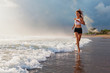 Active sporty woman run along ocean surf by water pool to keep fit and health. Sunset black sand beach background with sun. Woman fitness, jogging training and sport activity on summer family holiday.