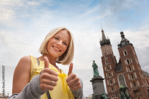 Fototapeta Female tourist in a yellow dress stands on a background of the church of St. Mary in Krakow. Basilica Mariacka. Krakow. Poland. obraz