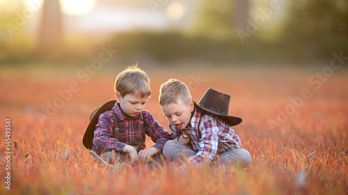 Valokuva  Children sit together in the meadow to rest
