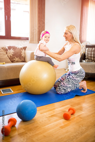 Fotografie, Obraz  Mother holding her baby on fitness ball in home