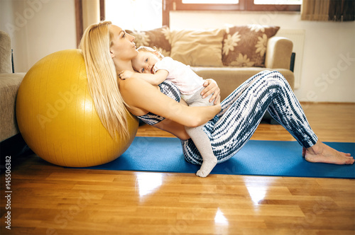 Fotografie, Obraz  Mother holding sleeping  baby while relaxing on fitness ball after exercise
