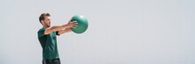 Banner. Medicine Ball Gym Workout Fitness Man Strength Training Arms Doing Front Raise Exercise For Shoulder Muscles. Upper Body Weighted Ball Workout At Fitness Centre. Panorama Crop With Copy Space.
