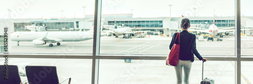 Traveler businesswoman at airport banner. Travel lifestyle. Travel tourist standing with luggage at airport lounge. Unrecognizable woman looking at window waiting at boarding gate before departure.