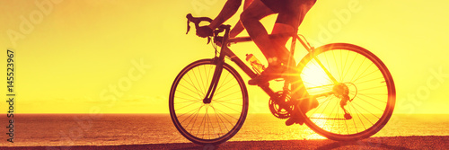 Cyclist biking on road bike sunset banner. Active healthy sports lifestyle athlete cycling.