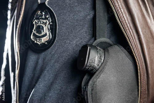 Valokuva  Closeup midsection of police officer with badge and gun in holster at night