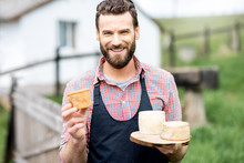 Portrait Of A Handsome Farmer In Apron Standing With Goat Cheeses Outdoors On The Rural Scene Background