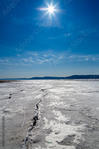 Poster Donkergrijs Spring melting of ice on the Volga River against the background of mountains and blue sky