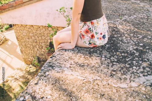 Fotografie, Obraz  Chica joven sentada en un tejado disfrutando de un atardecer de verano