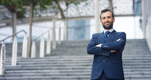 Fotomural A man in a suit, looks in camera and smiles proud and sure of himself