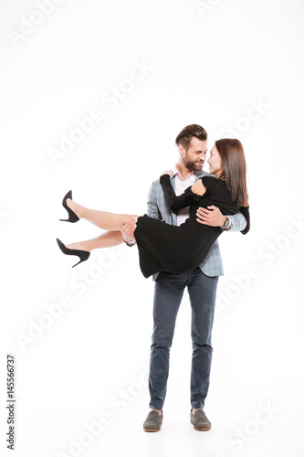 Smiling young loving couple standing isolated