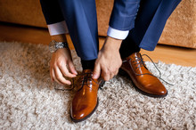 A Man Ties Up His Shoelaces On His Brown Shoes In The Room.