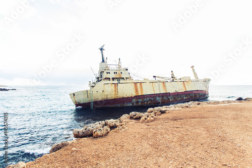 Spoed Foto op Canvas Schipbreuk Ship wreck surrounded by sea waves on beach, Cyprus