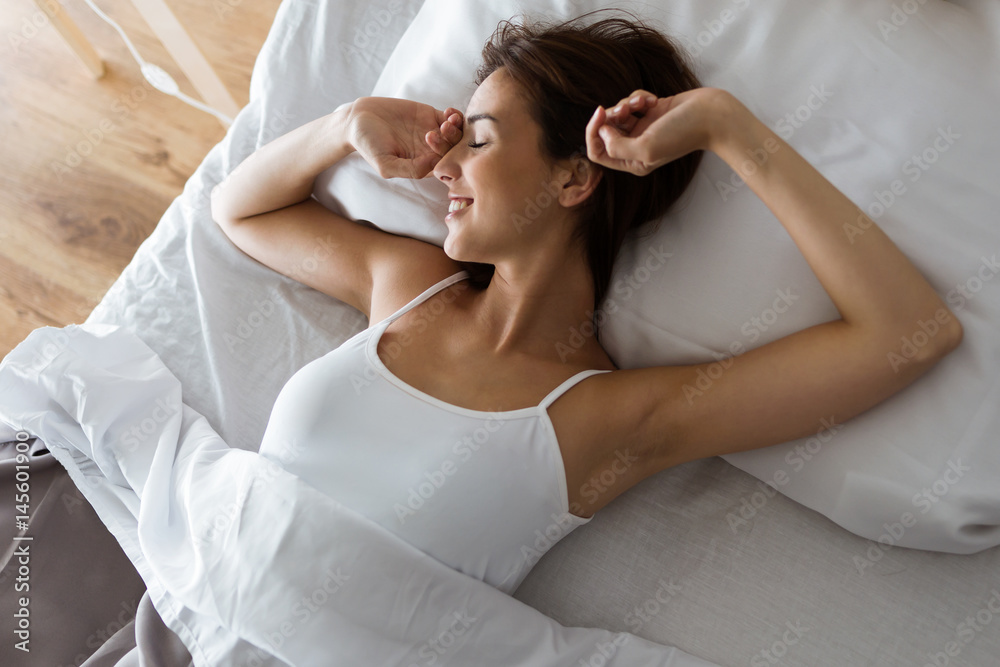 Fototapeta Beautiful young woman stretching in bed after wake up.