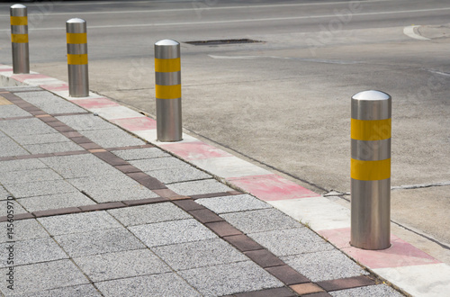 Fotomural Stainless Steel bollards on grey stone pavement