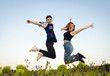 Happy couple, boyfriend and girlfriend jumping on beautiful green meadow in nature