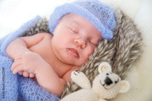 Fototapeta Sleeping newborn baby girl. Newborn baby in knitted cap and with a toy bear lying on a fur blanket. obraz na płótnie