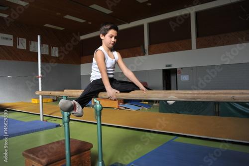 Foto op Canvas Gymnastiek 10-jähriger Junge beim Kunstturnen am Barren