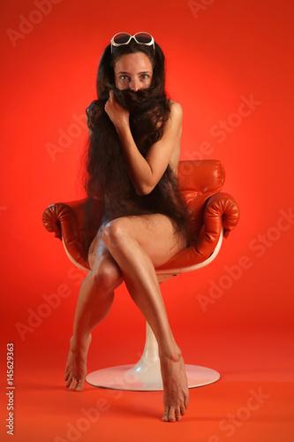 Eine nackte Frau bekleidet sich mit ihren langen Haaren