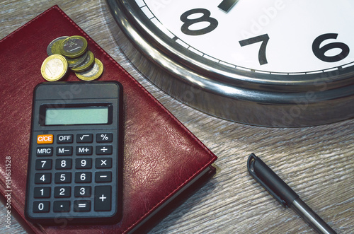 Office desk table with pen, calculator, book, money and wall