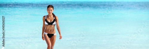 Obraz Asian bikini woman with slim body swimming in blue ocean banner of water copy space. Travel holiday girl relaxing on beach vacation. - fototapety do salonu