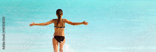 Obraz Happy bikini beach vacation woman running to ocean splashing water with open arms in freedom. Happiness carefree lifestyle banner with blue copyspace. - fototapety do salonu