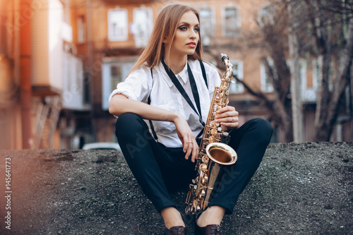 Obraz na plátně  Young attractive girl in white shirt with a saxophone sitting sits on the earth - outdoor