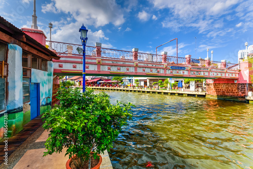 Green walkway along the historical river town of Malacca, Malaysia. Small pedestrian bridge under a sunny cloud blue sky in Melaka, a UNESCO World Heritage Site since 7 July 2008. Asia travel concept