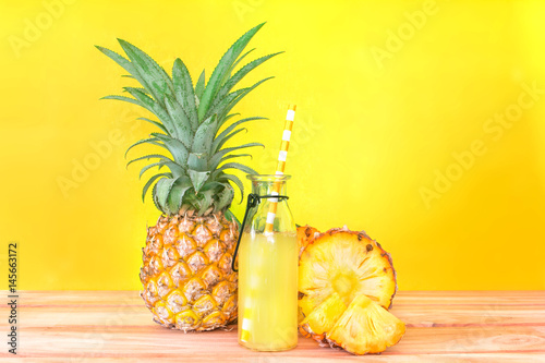 The Bottles of pineapple juice with sliced pineapple fruit on wooden table with vibrant yellow background , summer fruit drink concept