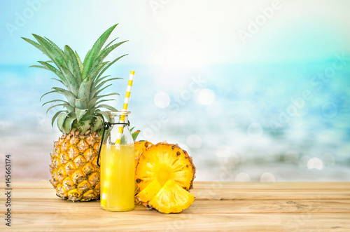 The Bottles of pineapple juice with sliced pineapple fruit on wooden table with abstract  blue sea background , summer fruit drink concept