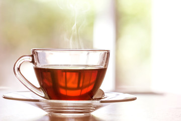 Close up warm black tea cup on wooden table in living room , relax with tea time concept