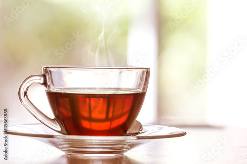 Poster The Close up warm black tea cup on wooden table in living room , relax with tea time concept
