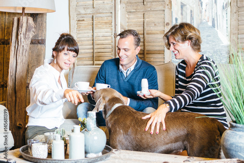 Fotografie, Tablou Couple with dog having tea with friend