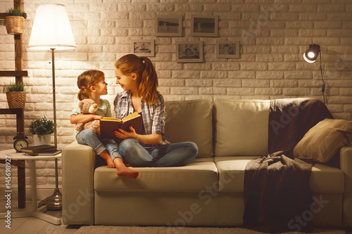 Photo  Family before going to bed mother reads to her child daughter book near a lamp i