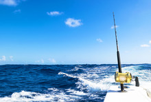 Fishing Rod In A Saltwater Boat During Fishery Day In Blue Ocean. Outdoor Fishing Concept. Ocean Fishing Boat