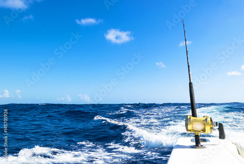 Poster Peche Fishing rod in a saltwater boat during fishery day in blue ocean. Outdoor fishing concept. Ocean fishing boat