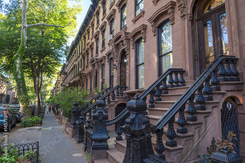 Scenic view of a classic Brooklyn brownstone block with a long facade and ornate stoop balustrades in New York City