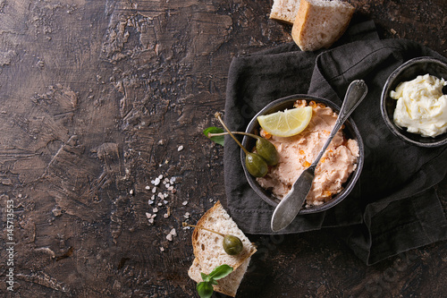 Poster Entree Black bowl of salmon pate with red caviar served with butter, sliced bread, capers, vintage knife and herbs on textile linen napkin over brown texture background. Top view.
