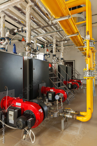 Interior of industrial gas boiler house with many pipes and boilers ...