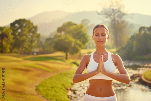 Yoga at park with view of the mountains and lake. Young woman with clasped hands. Concept of calm and meditation.