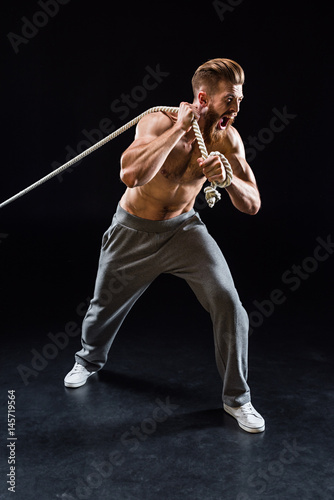 Fotografía  handsome bearded sportsman yelling and pulling rope isolated on black