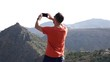 Man recording video, taking photo of canyon in mountains, super slow motion 240fps
