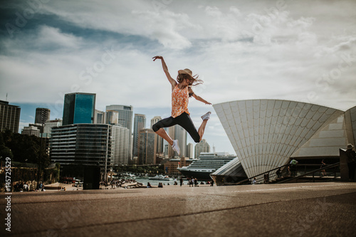 Staande foto Sydney Happy woman jumping in the air in Sydney, with the cityscape in the background. Australia.