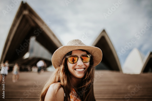 Cute smiling woman close up portrait, with Sydney Opera House building in the background.
