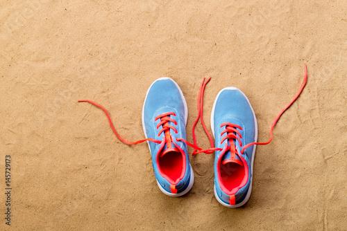 Fényképezés  Blue sports shoes laid on sand beach, studio shot