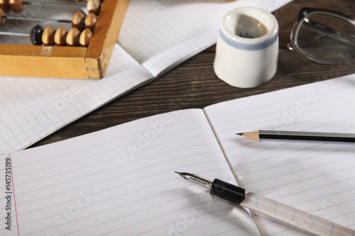 A penholder  with a pen and a simple pencil lie on an open notebook Fototapet