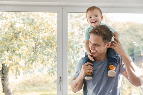 Valokuvatapetti Toddler boy on father's shoulders at home by window