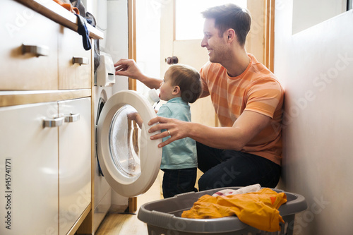 Photo Father and toddler son doing laundry at home