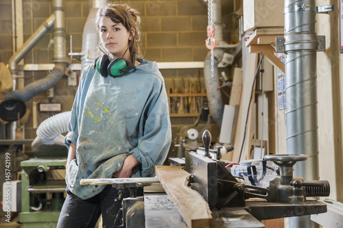 Portrait of young woman next to machinery in wood workshop Wallpaper Mural