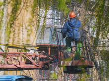 Worker In Special Clothes On Lift Machine