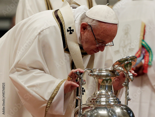 Pope Francis blows in an amphora to bless the oil of the